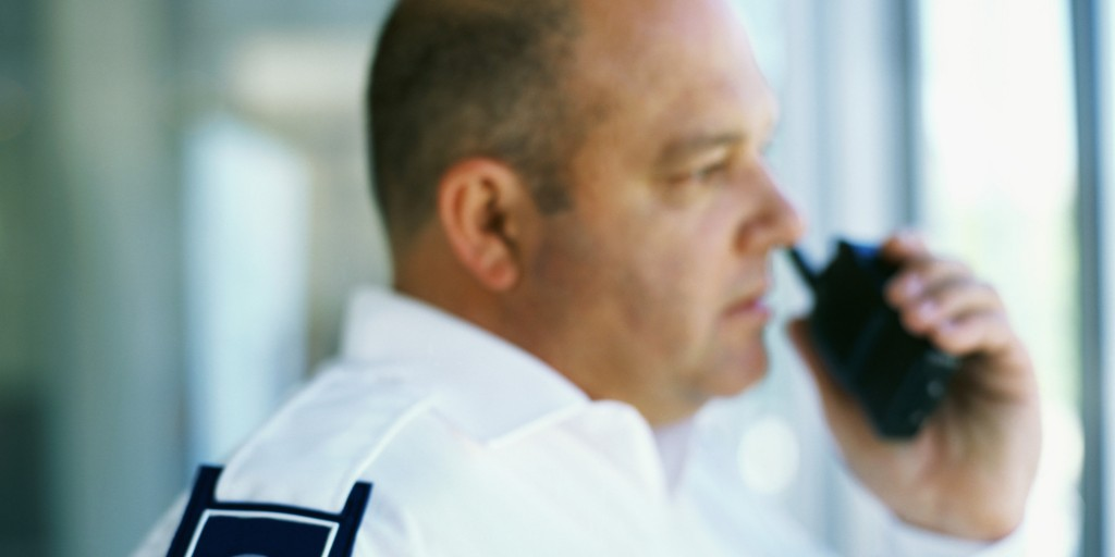 side profile of a security guard talking on a walkie talkie in an office
